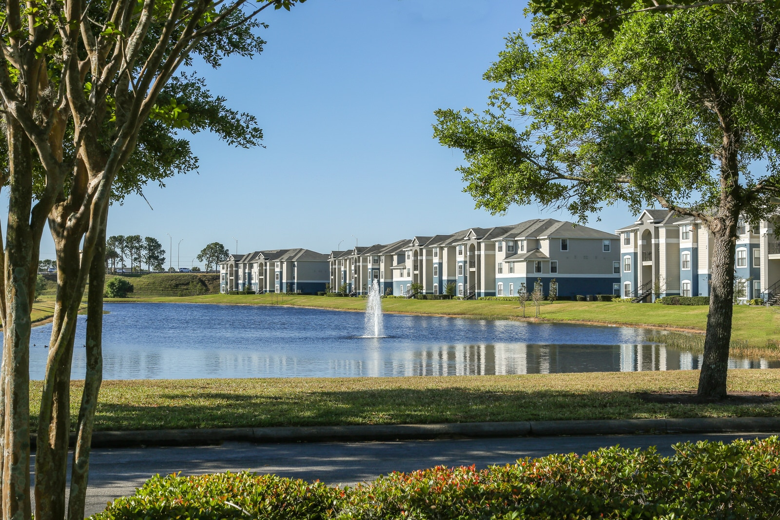 landscape shot of apartments in distance behind lake
